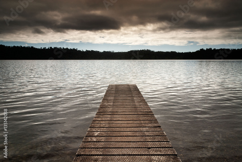 New Zealand - Wooden jetty leads into an empty lake on cloudy mo