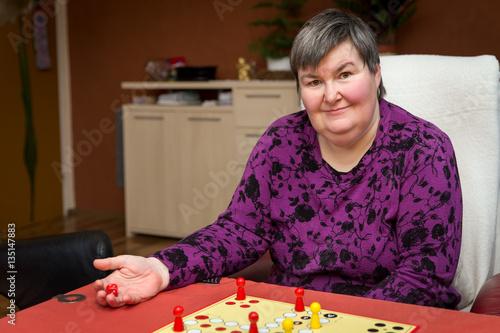 Foto  geistig behinderte Frau spielt ein Brettspiel, Alternative Thera