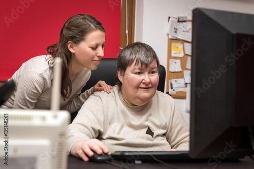 Betreuerin und geistig behinderte Frau lernen am Computer Wallpaper Mural