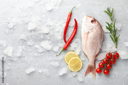 Poster Fish Fish cooking: fresh red Japanese seabream, lemon slices, chili pepper, cherry tomatoes and rosemary on gray stone background
