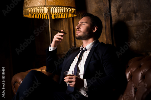 Handsome man drinking whiskey and smoking cigar Canvas Print