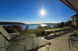 Large spacious deck of grey waterfront home at sunset
