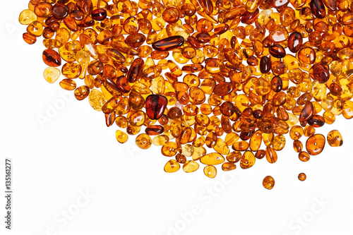Tableau sur Toile Dark yellow amber stones on a white background.