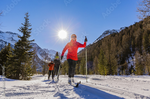 Fotografia  A family group of cross country skiers on a sunny winter morning
