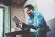 Leinwanddruck Bild - Bearded smiling African man using tablet for video conversation while relaxing on sofa in modern office.Concept of young business people working at home.Blurred background.Selective focus.