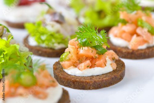 Cadres-photo bureau Buffet, Bar Leckeres Fisch-Fingerfood mit Lachstatar, Matjestatar und Forellencreme mit Preiselbeeren - Finger food with salmon tartar, trout mousse with cranberries and herring salad on pumpernickel