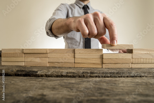 Fototapety, obrazy: Fingers placing wooden block on orderly stack