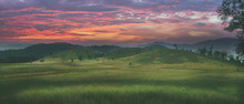 ' Grassy Hill ', Beautiful Natural Green Grass Meadow Field Hill At Dawn.colorful Sky At Sun Rises.
