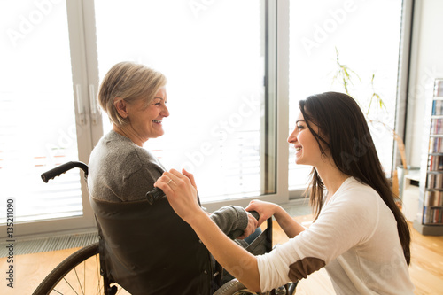 Fotomural Disabled senior woman in wheelchair with her young daugher.