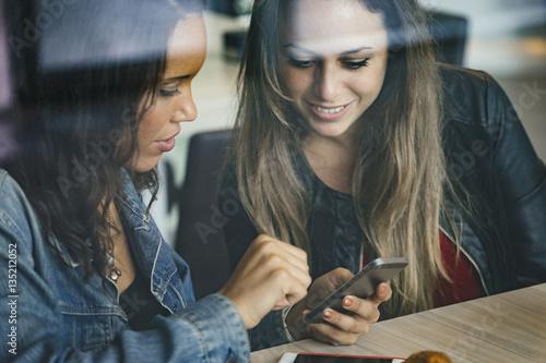 Fotografija  two female mixed race friends having fun together