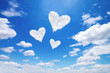 three white heart shaped clouds on blue sky
