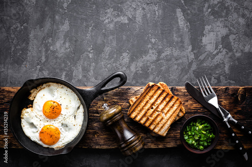 La pose en embrasure Ouf fried eggs on dark background with space for text
