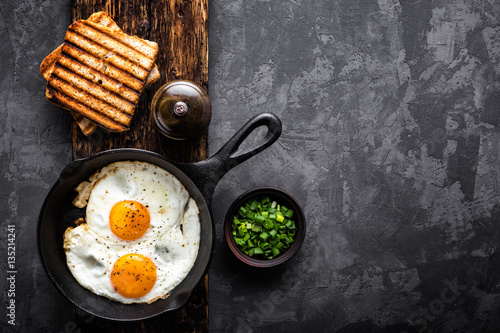 Poster Ouf fried eggs on dark background with space for text