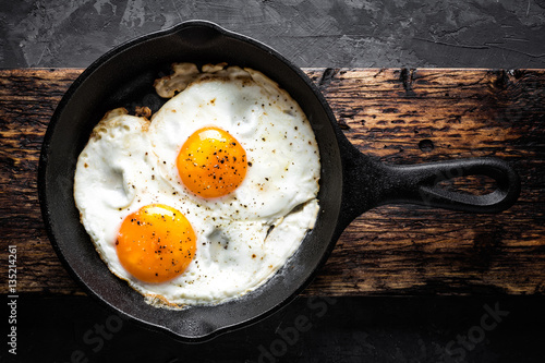 Photo fried eggs in black pan