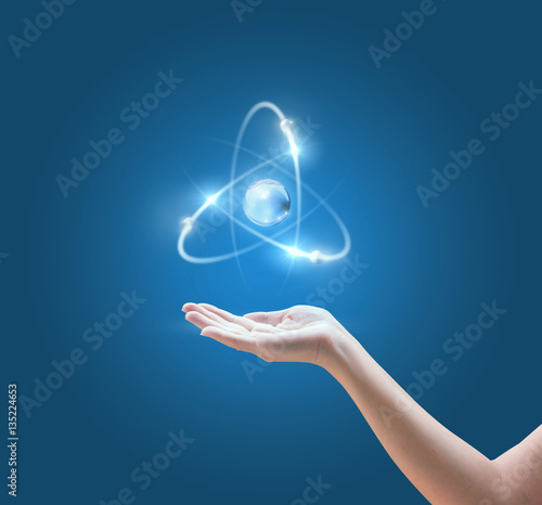 Hand with the atom image on blue background.