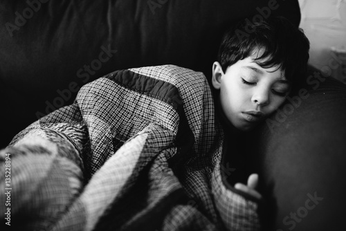 Boy asleep, wrapped in patterned duvet, black and white