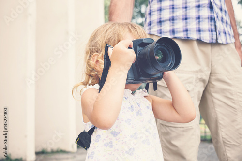 Fototapeta Little girl holding a camera and taking pictures. obraz na płótnie