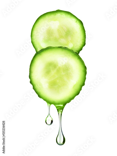 drop flowing from two fresh slices of cucumber on white backgrou
