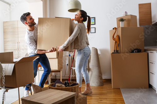 Young couple carrying big cardboard box at new home.Moving house. Wallpaper Mural