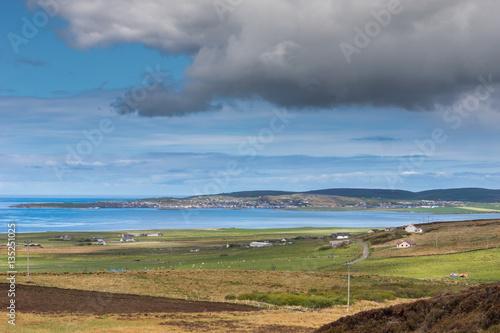 Spoed Foto op Canvas Inspirerende boodschap Orkneys, Scotland - June 5, 2012: Look west to the town of Stromness across arm of Atlantic Ocean under blue cloudy sky. Brown fields and green meadows in front. Blue ocean.