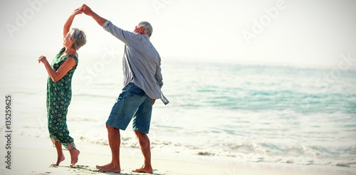 Senior couple dancing at beach