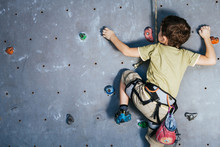 Little Boy Climbing A Rock Wall Indoor