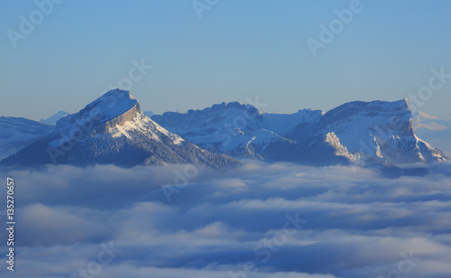 The snow covered Chartreuse mountains rising out of the clouds on a winter morning Canvas Print