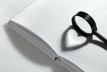Shade In The Form Of Heart On The Magnifying Glass On The Background Of An Open Book.