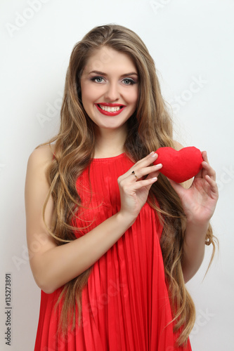 Happy girl holding a red decorative heart.