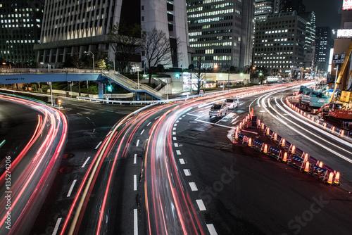 Plakat Jasne i świecące życie nocne Japonii widać na zdjęciu. Na zdjęciu widać kilka wysokich budynków i świecących ulic. Noce w Japonii są po prostu niesamowite.