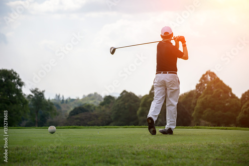 Deurstickers Golf Golfers men player golf hit swing shot on course sunset.