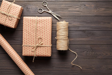 The concept of wrapping gifts in rustic style on birthday or holidays with copy space. Wrapping paper, scissors, twine. Dark wooden background. Flat lay. View from above.
