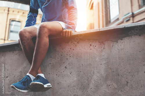 Fotografia  Male athlete in blue running shoes sitting and resting after street workout sess