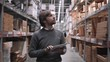 Man using tablet pc against shelves with boxes in warehouse. Handsome merchandiser in modern stock center.