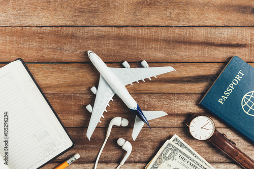 Photo  Preparation for Traveling concept, pencil, watch, money, passport, airplane, noted book,  earphone, on a vintage wooden background with copy space