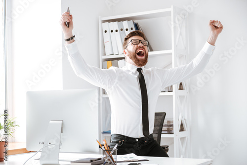 Fotografiet  Happy businessman make winner gesture.