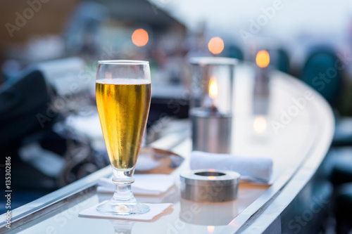 Photo  Glass of beer in Bangkok city view point from rooftop of building, blue sky and city light, Bangkok is the most populated city in Southeast Asia