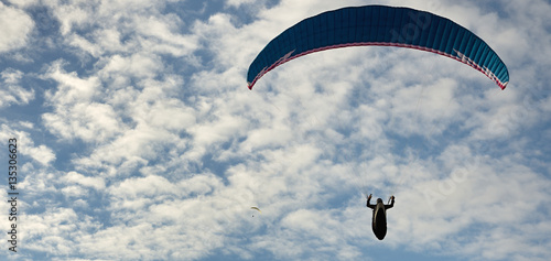 Tuinposter Luchtsport Paragliding flight with blue sky and some clouds