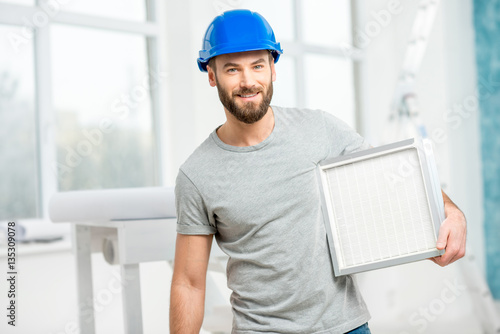 Fotografía  Worker holding air filter for installing in the house ventilation system