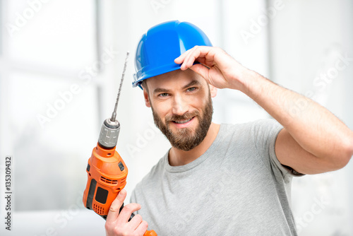 Portrait of a handsome repairman with drill and helmet in the bright interior