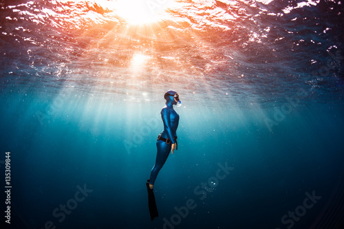 Tela Woman free diver ascending from the depth in a tropical clear sea