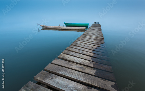 Photographie  meditative landscape with old wooden pier and wooden boats, long exposure, infin