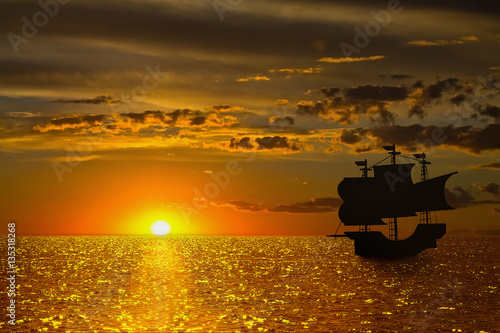 Deurstickers Oranje eclat seascape with a golden setting sun and the silhouette of a sailboat