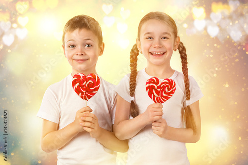 Cute Kids Little Boy And Girl With Candy Red Lollipop In Heart Shape