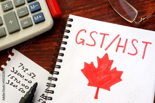 Fotografie, Tablou  GST / HST written in a note on a wooden surface.