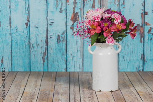 Bouquet of flowers in vintage white vase in rustic setting