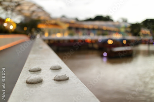 City on the water blurred background with bokeh of metal bridge and restaurant by river