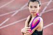Frau beim Tapen mit Physio-Tape auf der Laufbahn eines Sport-Stadions