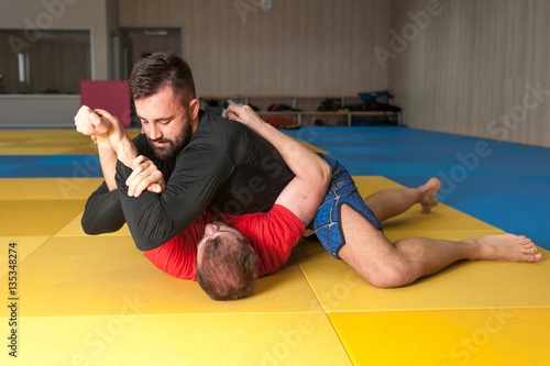 MMA fighter with beard arm locking his opponent on tatami