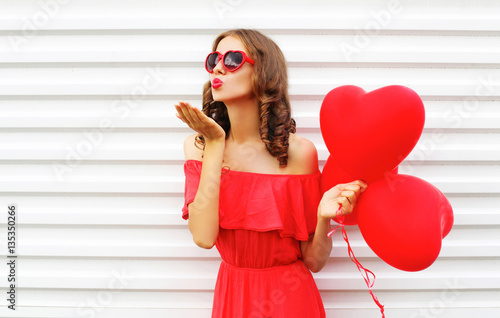 Photo  Portrait woman in red dress sends air kiss with balloon heart sh